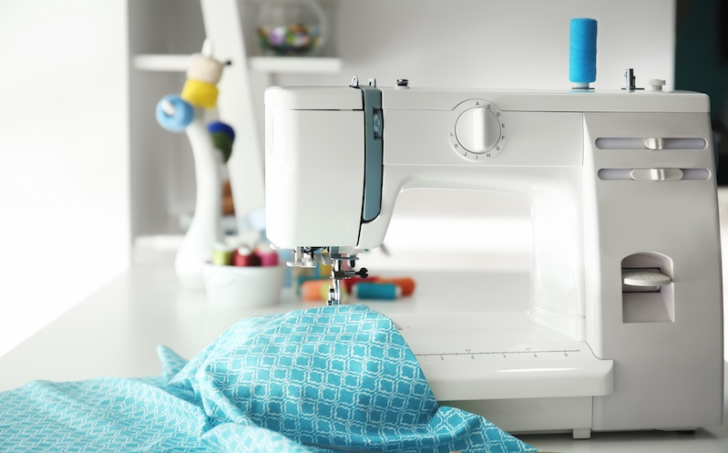 Sewing machine with thread and fabric on table