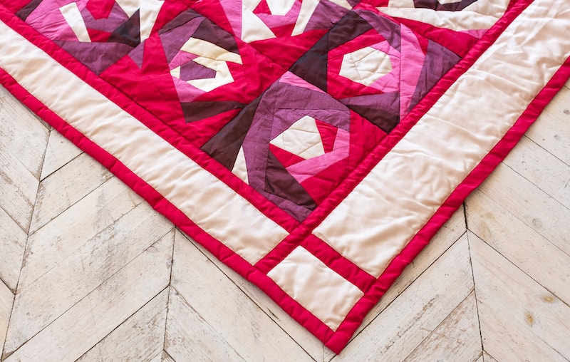 modern quilt pattern blanket on a wooden floor