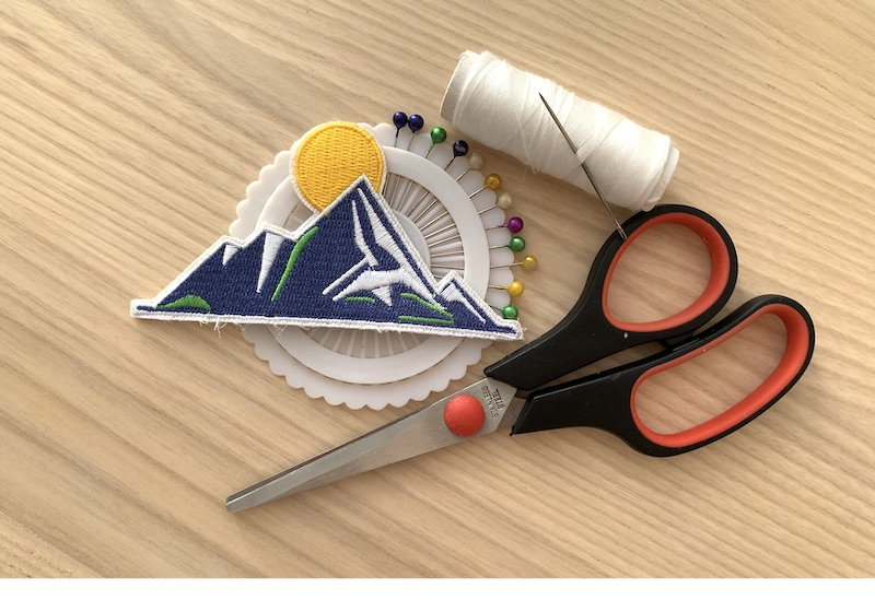 patch, sewing pins, white thread with needle and scissors on a wooden table