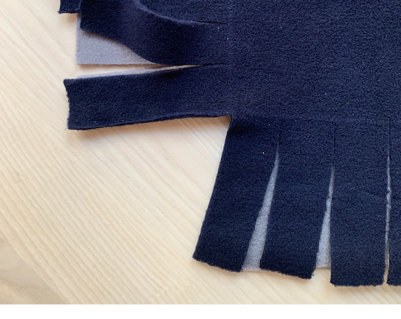 fringes cut out on two sides of a fleece fabric