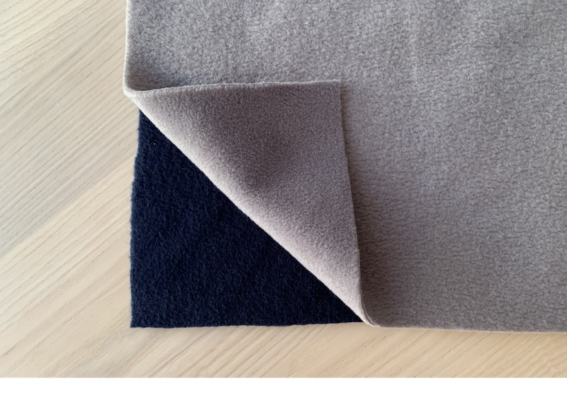 two pieces of fleece fabric on a wooden table
