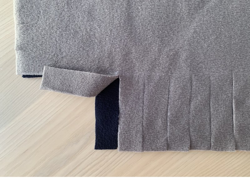 a piece of fleece fabric with fringes cut out on one side