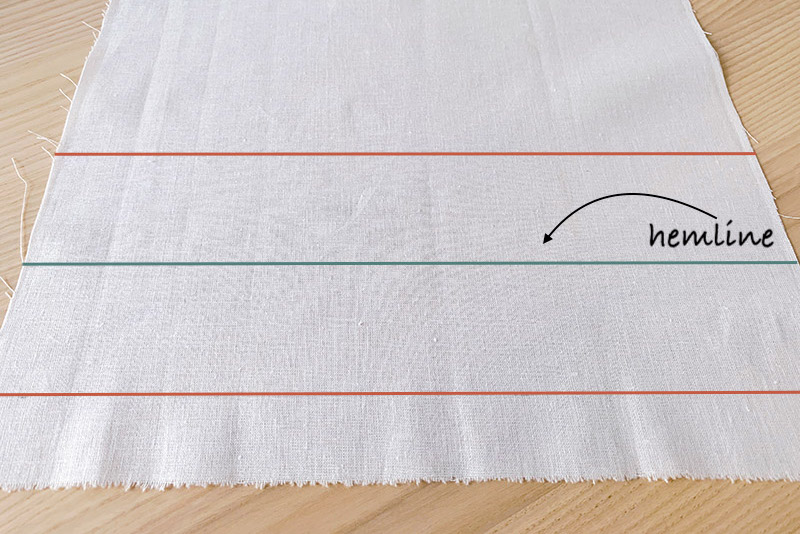 a piece of white fabric with marked hemline