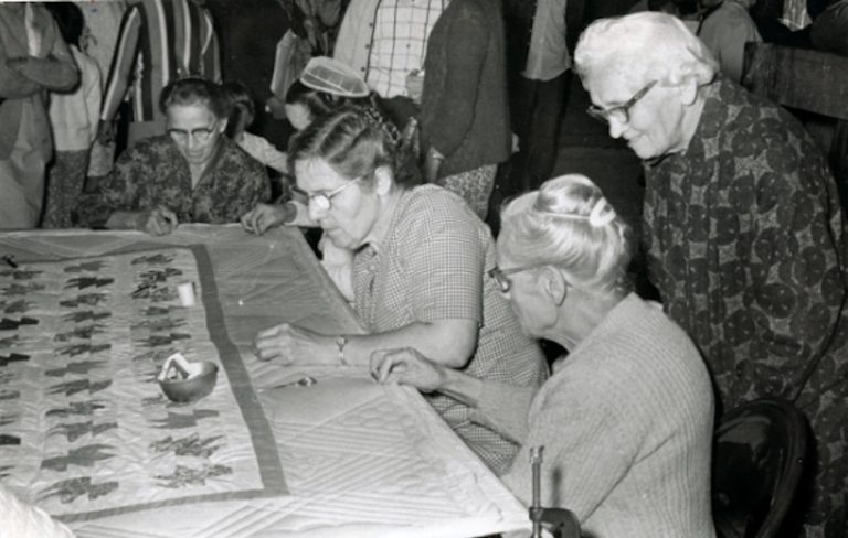 an old photograph of women quilting