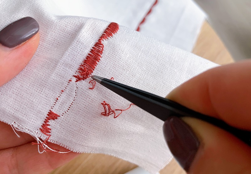 pulling out threads from embroidery stitch with tweezers