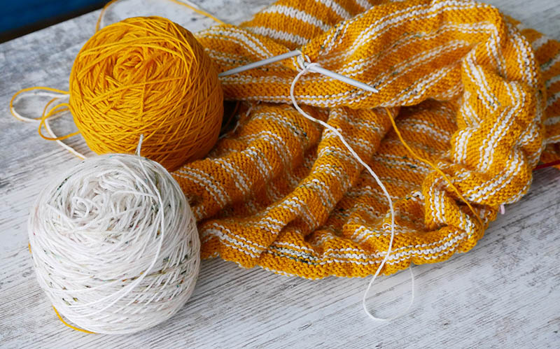 white and yellow yarn cakes on an unfinished knitting